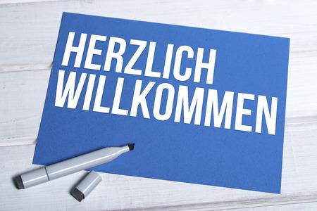 board marker: blue board with german word Herzlich Willkommen written in white and black marker lying on top Stock Photo