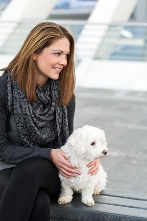 cuddles: happy pretty young woman cuddles white maltese dog