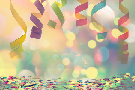 colourful paper streamer hanging from top with confetti on the bottom for celebration Standard-Bild