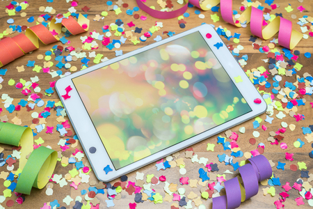 celebration event: colourful confetti and paper streamers on wooden table with colourful template on tablet