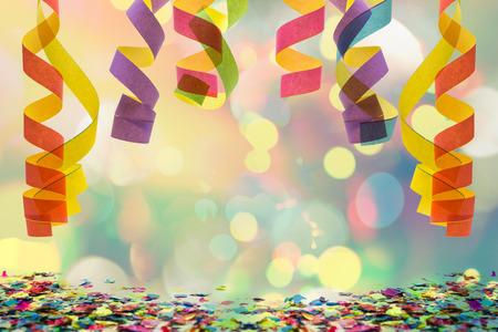 carnival: colorido streamer de papel colgando de la parte superior con confeti en el fondo de celebración Foto de archivo