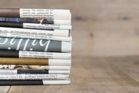 Variety of daily newspaper issues with wood in background Imagens