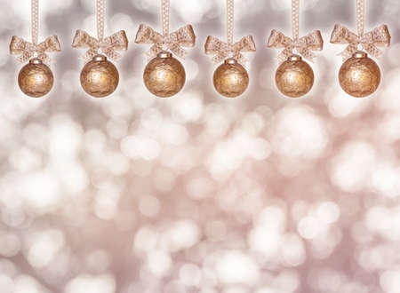 hanging golden christmas balls with ribbon in front of unsharp background Stock Photo