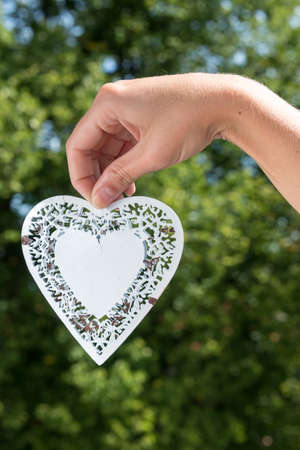 held down: White metal heart hanging down held by hand in a park during summer as a closeup
