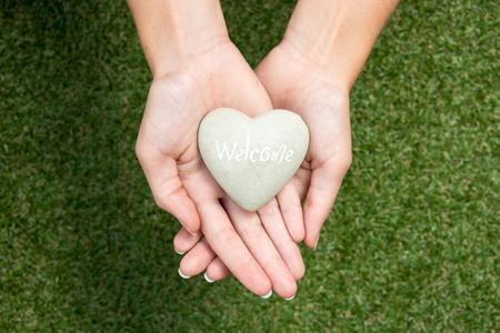 friendliness: Corazón de piedra que tuvo lugar en las manos cruzadas sobre prado simboliza acogedor y amabilidad