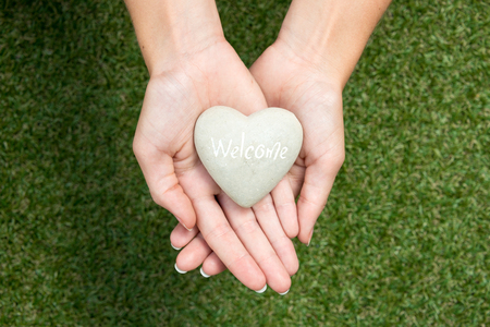 friendliness: Heart made of stone held in crossed hands above meadow symbolizing welcoming and friendliness Stock Photo