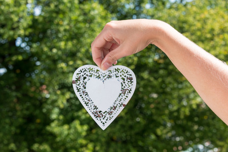 held down: White metal heart hanging down held by hand in a park during summer