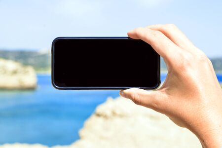 womans: Smart phone held by womans hand with pointing fingeron screen in holidays in front of sea