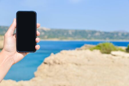 woman's hand: Smart phone held by womans hand with pointing fingeron screen in holidays in front of sea