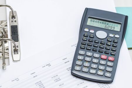 spreadsheets: Charts with calculator lying on top of opened folder Stock Photo