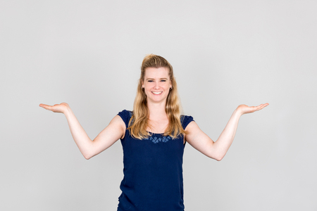 both: Studio shot of young woman presenting with both her hands palms up