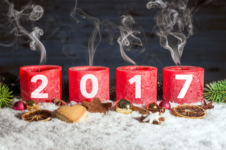 fume: Four red blown out advent candles with fume and 2017 written in front of black background as template Stock Photo