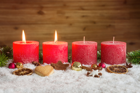 Four red advent candles with two candles lit and christmas decoration lying in snow as template Zdjęcie Seryjne