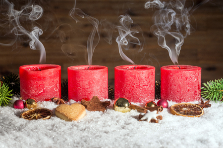 fume: Four red blown out advent candles with fume in front of brown background as template