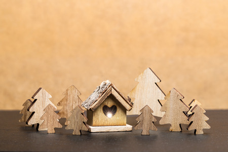 Carved wooden fir trees and wooden cottage with heart  in front of brown background as template