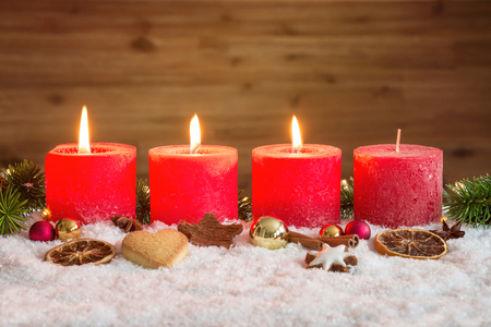 Four red advent candles with three candles lit and christmas decoration lying in snow as template Banco de Imagens - 65126113