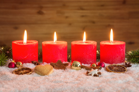 Four red advent candles with four candles lit and christmas decoration lying in snow as template Imagens
