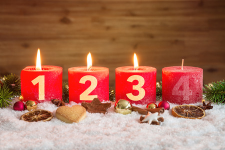 Four numbered red advent candles with three candles lit and christmas decoration lying in snow as template