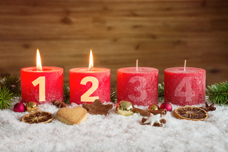 Four numbered red advent candles with two candles lit and christmas decoration lying in snow as template