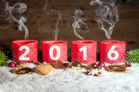 fume: Four red blown out advent candles with fume and 2016 written in front of brown background as template