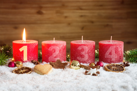 Four numbered red advent candles with first candle lit and christmas decoration lying in snow as template