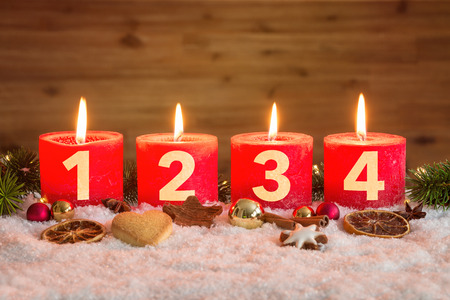 Four numbered red advent candles with four candles lit and christmas decoration lying in snow as template