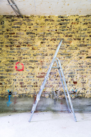 Old brick wall in a building with ladder prepared for construction and renovation