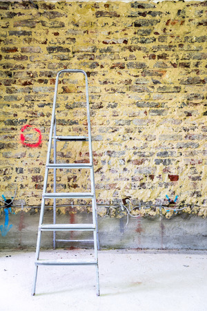 modernize: Old brick wall in a building with ladder prepared for construction and renovation