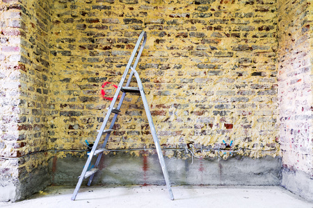 modernise: Old brick wall in a building with ladder prepared for construction and renovation