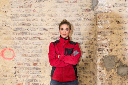 workwoman: Concentrated craftswoman in front of brick wall that is in need of renovation