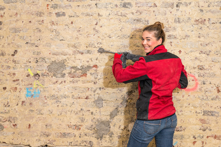 workwoman: Committed smiling craftswoman with a caulking hammer in front of brick wall that is in need of renovation