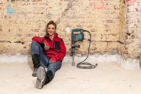 Committed smiling craftswoman sitting on the floor against brick wall that is in need of renovation with caulking hammer