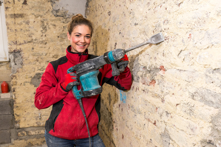 Committed smiling craftswoman with a caulking hammer in front of brick wall that is in need of renovation