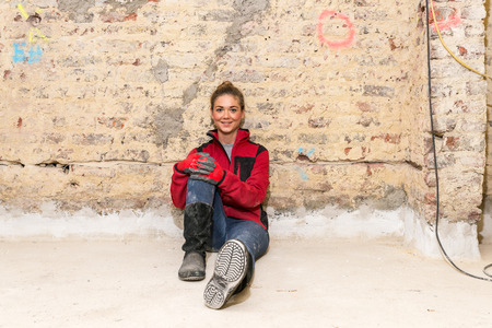 workwoman: Committed smiling craftswoman sitting on the floor against brick wall that is in need of renovation