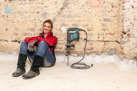 workwoman: Committed smiling craftswoman sitting on the floor against brick wall that is in need of renovation with caulking hammer