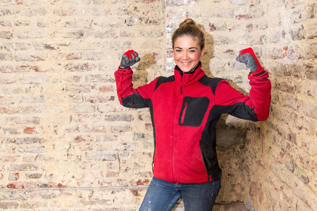 workwoman: Smiling craftswoman full of zest for action in front of brick wall that is in need of renovation Stock Photo