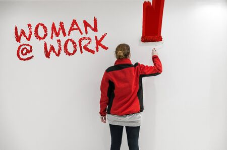 red paint roller: Paintress with red paint roller painting a wall as background with woman @ work writing Stock Photo