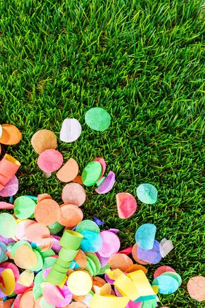 wedding feast: Close-up of colorful confetti and streamers on grass as template for birthday celebration or carnival