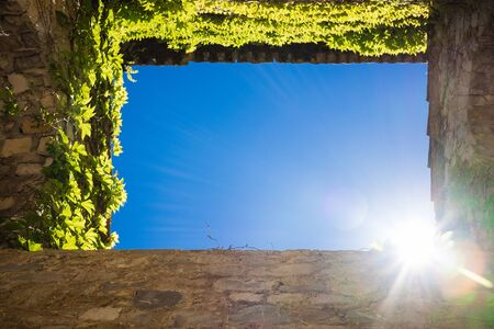 pearly gates: Upright shot from ground into blue sky framed by four walls showing sun as template Stock Photo