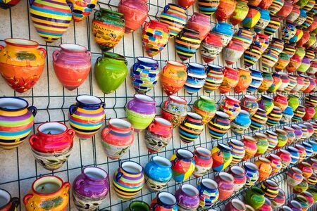 conglomeration: Conglomeration of colorful flowerpots of pottery hanging decoratively at wall