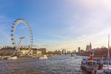 river: Cityscape of London with big giant wheel, River Thames and Houses of Parliament with Big Ben against blue sky Editorial