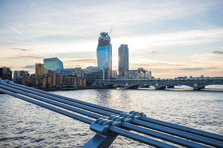 Londons skyline with view at Blackfriars bridge and river Thames from Millennium Bridge during sunset Stock Photo