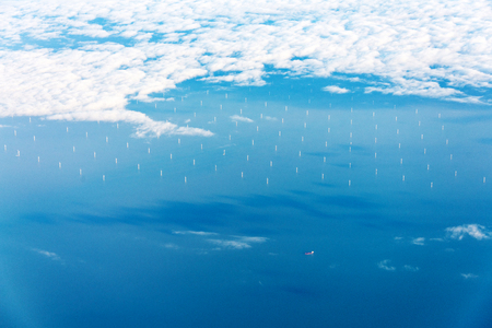planos electricos: Offshore wind farm from above in blue water and with white clouds at horizon