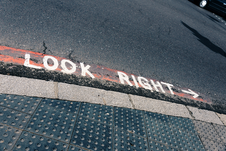 Look right hint painted on asphalted road as safety warning in London, United Kingdom Stock Photo