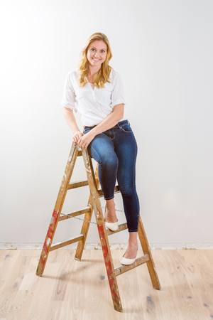 Young woman sitting on top of a wooden ladder in front of white background as template