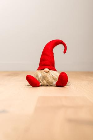 Rote sitzende Weihnachtselfe mit der spitzen Kappe lokalisiert als Schablone Standard-Bild - 90094052