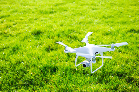 Flying white professional quadcopter drone camera with green grass in background