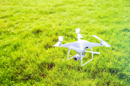 Photo of a flying white professional quadcopter drone camera with green grass in background