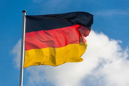 Closeup of single german flag waggling in the wind in front of blue sky