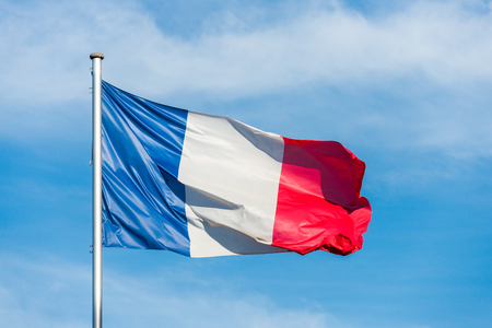 Closeup of single french tricolor flag waving in the wind in front of blue sky Stock Photo